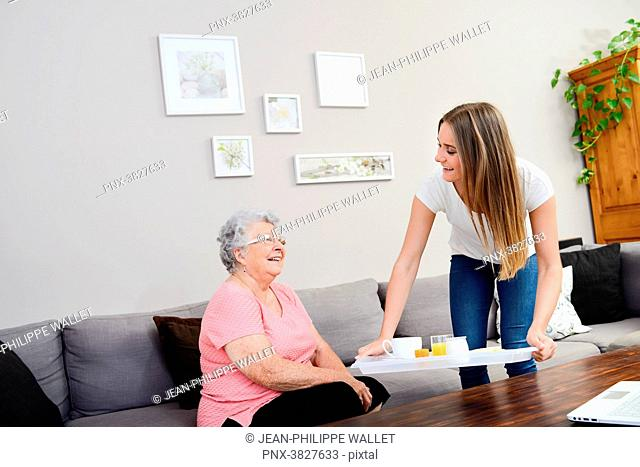 Cheerful young girl serving breakfast to elderly woman at home