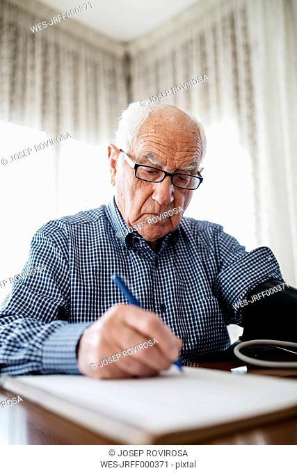 Senior man controlling his blood pressure and writing down the result