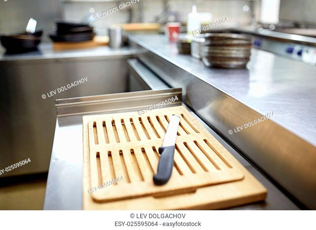 cooking and public catering concept - cutting board and knife at restaurant kitchen