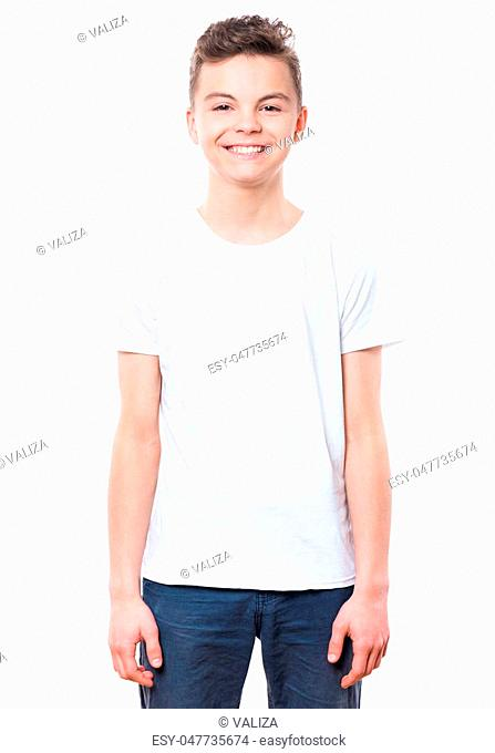 White t-shirt on teen boy. Handsome caucasian smiling child, isolated on a white background. Concept of childhood and fashion or advertisement design