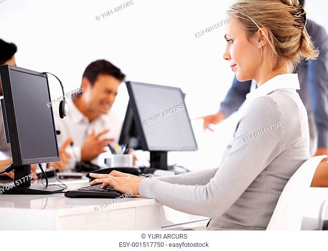 Beautiful business woman working on computer with colleagues in background