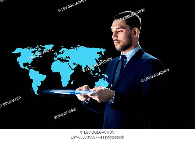 business, people and modern technology concept - businessman in suit with transparent tablet pc computer and world map projection over black background