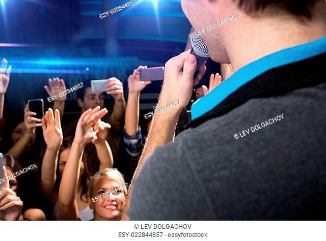 holidays, music, nightlife and people concept - close up of singer singing on stage over happy people crowd taking picture by smartphones and waving hands at...