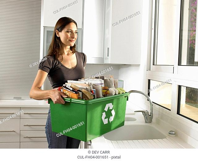 Woman holding recycling box, smiling