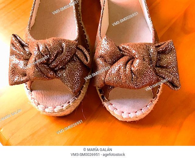 Pair of golden sandals. Close view