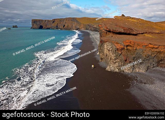 Black sand beach with Lundadrangur Rock Arch in Dyrholaey, South