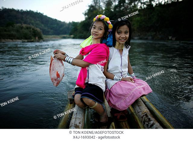 Two Longneck girls with a fish on a boat Approximately 300 Burmese refugees in Thailand are members of the indigenous group known as the Longnecks The largest...