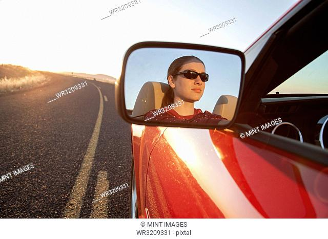 A young Caucasian woman reflected in side mirror of a convertible sports car on the highway