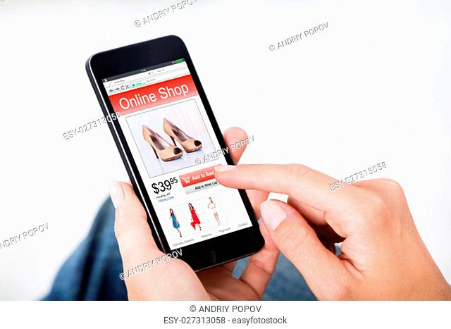 Close-up Of Woman Hand Shopping Online Purchasing Footwear Using Mobile Phone