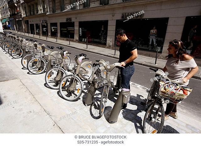 France. Paris. People picking up bicycle in a 'Velib' bicycle station. 'Velib' is a new self-service bicycle transit system start to serve Parisians and...