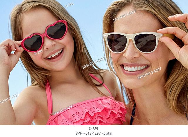 MODEL RELEASED. Mother and daughter wearing sunglasses on the beach, portrait