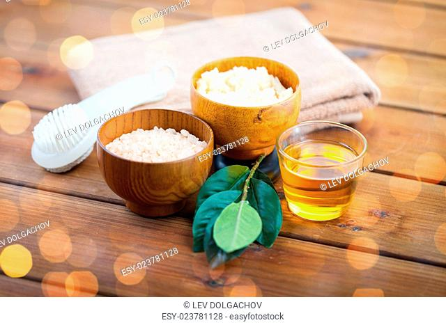 beauty, spa, body care, natural cosmetics and bath concept - close up of himalayan pink salt and body scrub with brush on wooden table