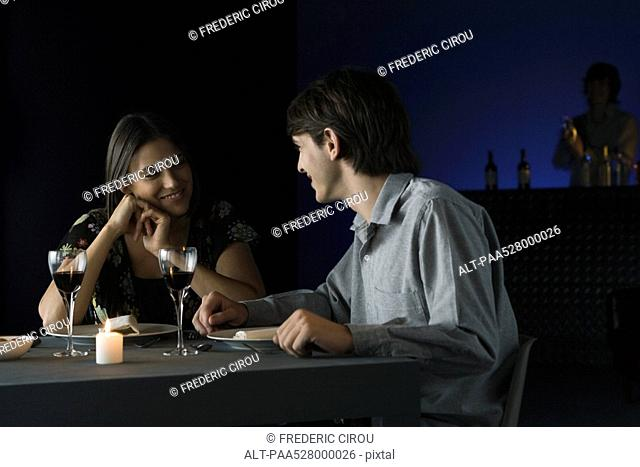 Couple having conversation over dinner at restaurant, smiling at each other