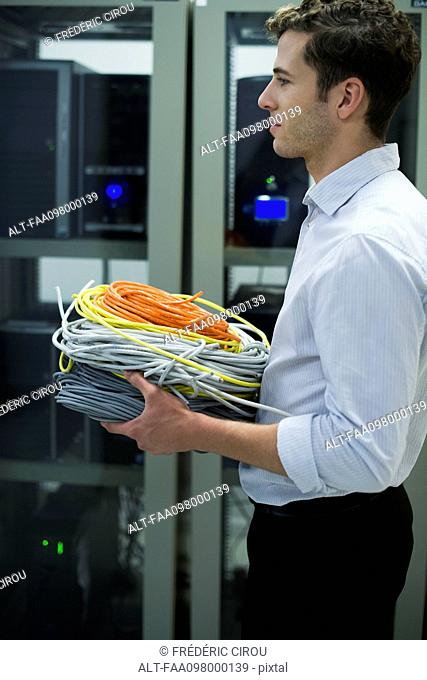 Computer technician carrying coils of networking cables into server room