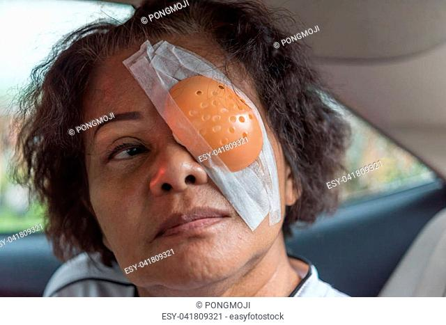 Patient asian elder women 60s with black hair and wrinkled on face show her eyes with eye pad and eye shield after cornea surgery (lasik) by ophthalmologist in...