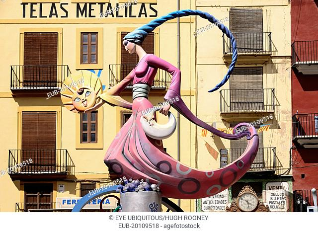 Papier Mache figure of a lady in a pink dress holding a replica of the sun during Las Fallas festival
