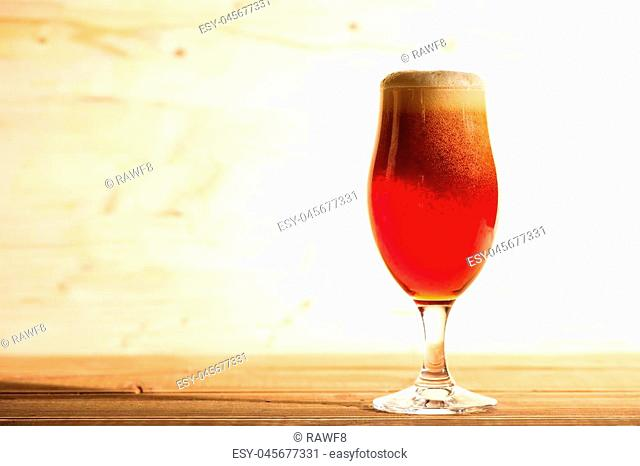 A glass full of red beer on a wooden background, copy space