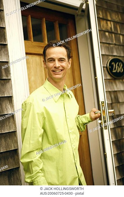 Portrait of a mature man holding a door handle and smiling