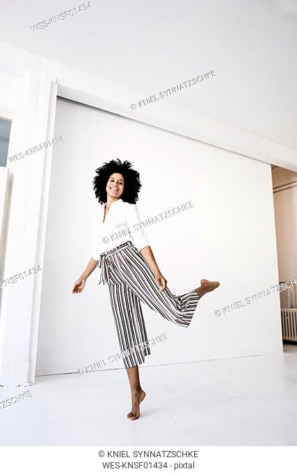 Young woman dancing in front of white door