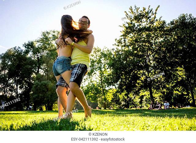 Couple dancing bachata in summer park backlit training dip figure