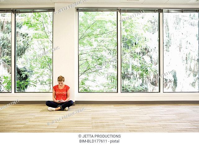 Caucasian businesswoman sitting in empty office