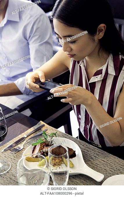 Woman using smarphone to photograph her meal in restaurant