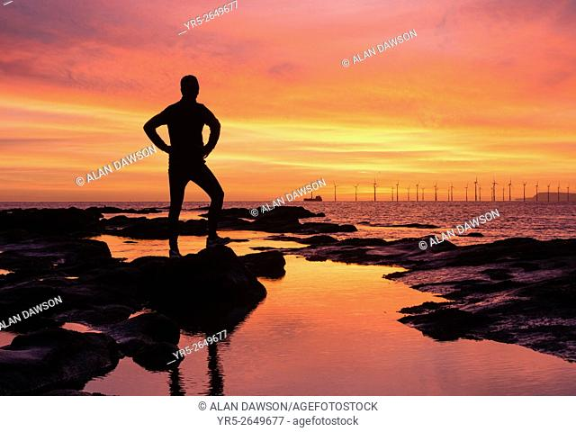 Seaton Carew, north east England, United Kingdom. Weather: Jogger watching the sun rise over the North sea on Seaton Carew beach