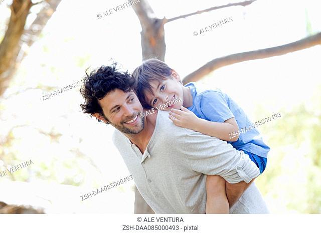 Father giving little boy piggyback ride