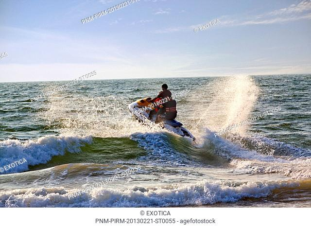 Tourists riding jet boat in a sea, Candolim, Bardez, North Goa, Goa, India