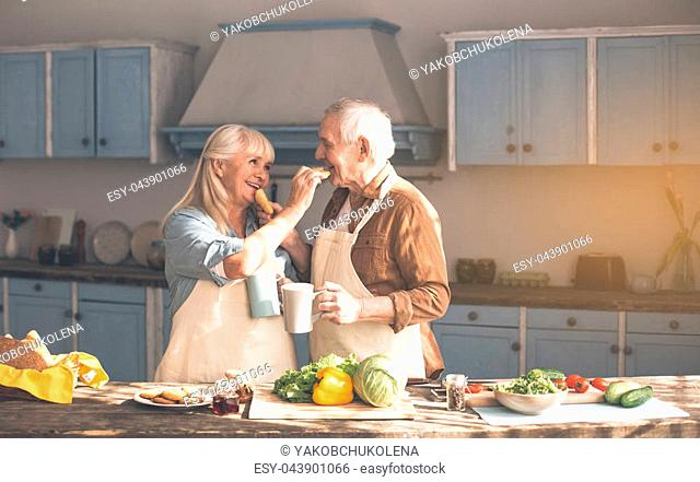 Affectionate senior married couple is feeding each other by sweet pastry with love. They are holding cups of coffee and smiling while standing in kitchen