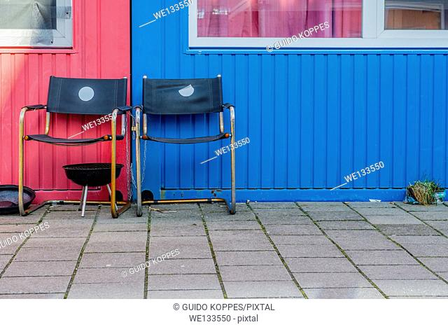 KSM Island, Amsterdam, Netherlands. Two old dining rom chairs in front of old cargo containers, which have been transformed into student dormitory