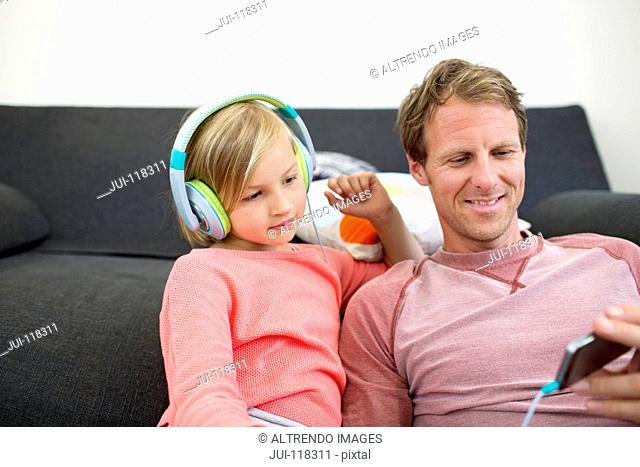 Father And Daughter Listening To Music On MP3 Player At Home