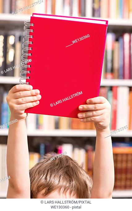 Young child holding red book over head in a library