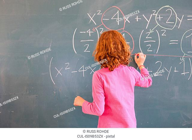 Rear view of primary schoolgirl answering equation on classroom blackboard