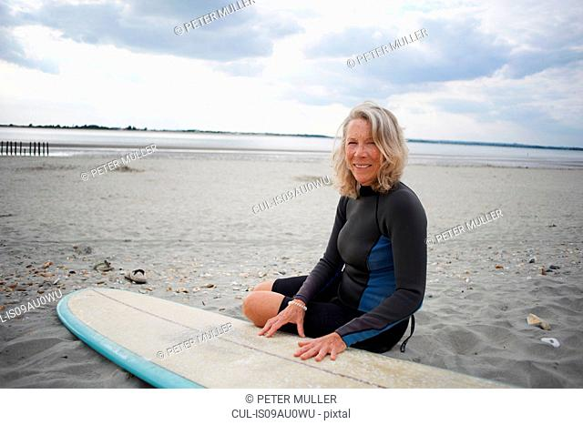 Portrait of senior woman sitting on beach next to surfboard