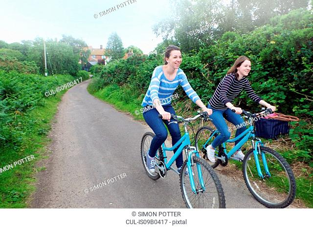 Two young adult sisters cycling along country lane