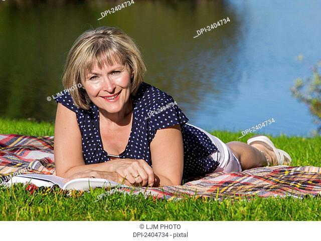 Mature woman relaxing and reading in Hawrelak Park; Edmonton, Alberta, Canada