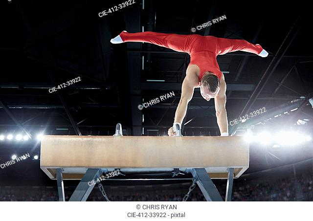 Male gymnast performing upside-down handstand on pommel horse in arena
