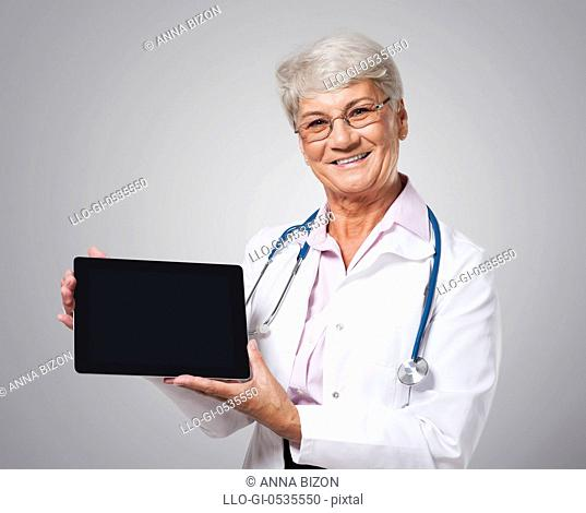 Candid female doctor showing screen of digital tablet. Debica, Poland