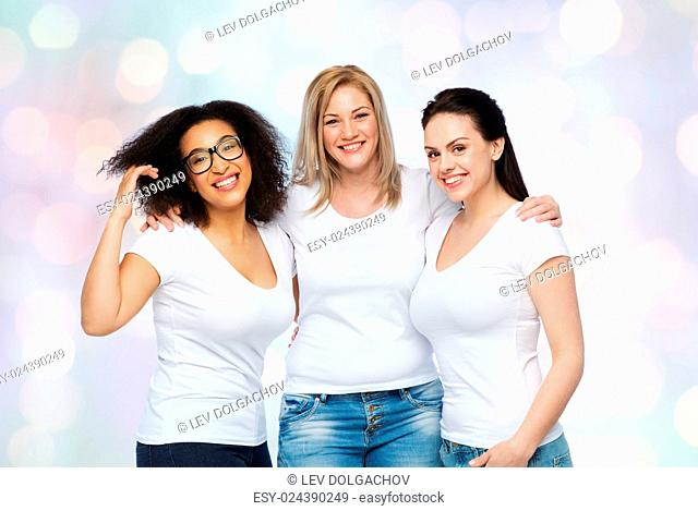 friendship, diverse, body positive and people concept - group of happy different size women in white t-shirts hugging over holidays lights background