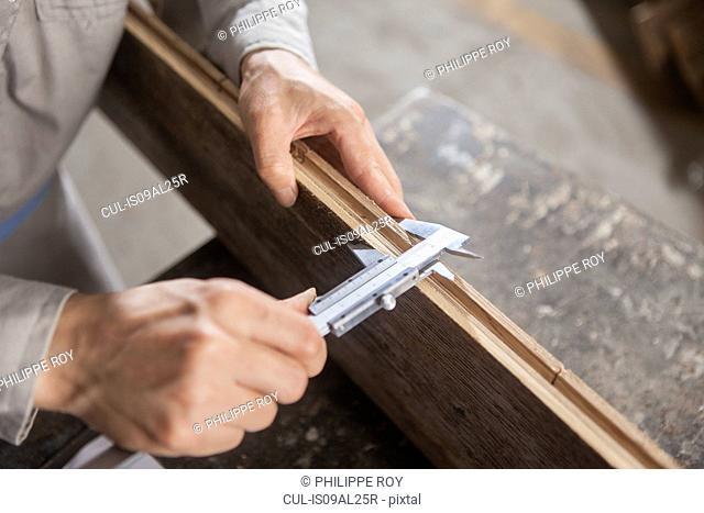 Carpenter measuring wood plank with vernier caliper in factory, Jiangsu, China