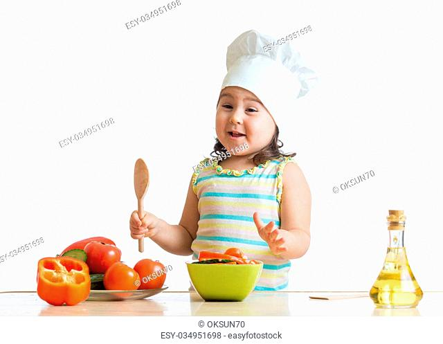 Funny kid girl preparing healthy food in the kitchen