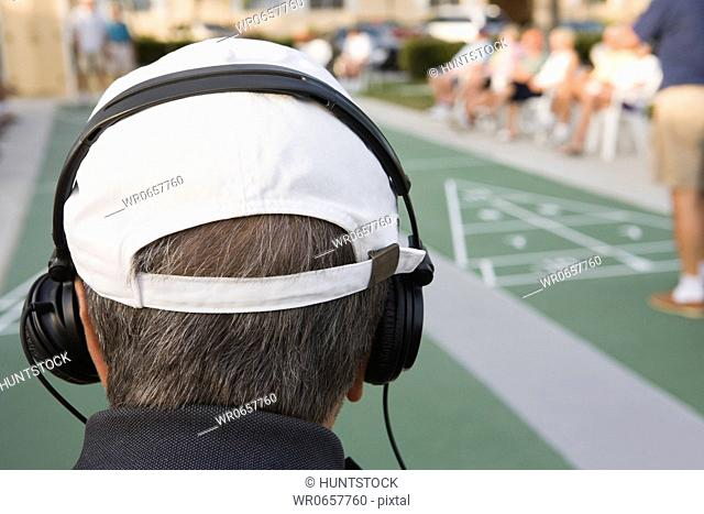 Rear view of a senior man wearing headphones