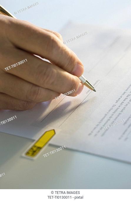 Close up of man signing paperwork