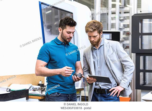 Two men with tablet talking in modern factory