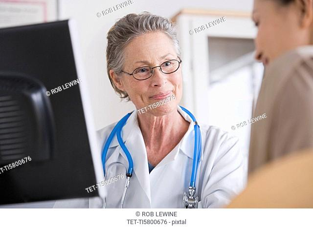 Smiling female doctor talking to patient in her office