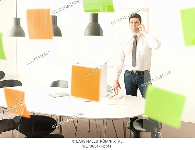 Businessman looking at glass wall with adhesive notes. Conceptual image of business planning