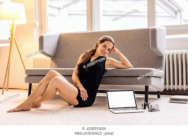 Portrait of smiling woman leaning on couch next to laptop