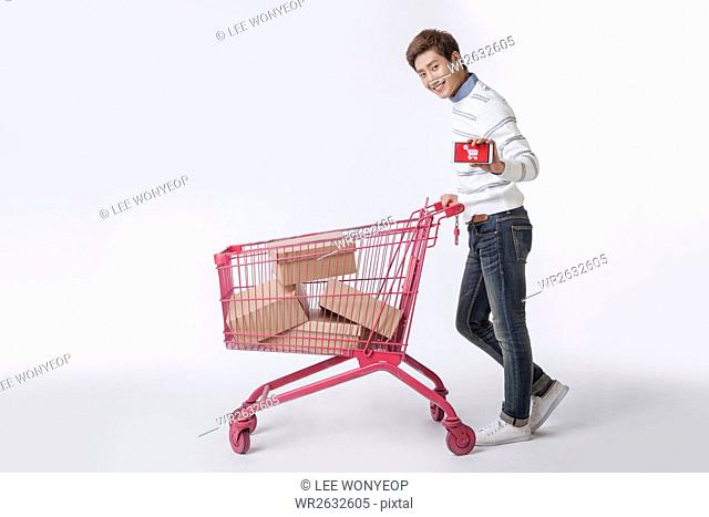 Side view of young smiling male shopper showing smartphone