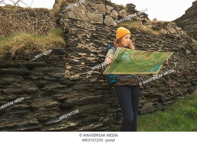 Female hiker leaning against the rock and reading a map